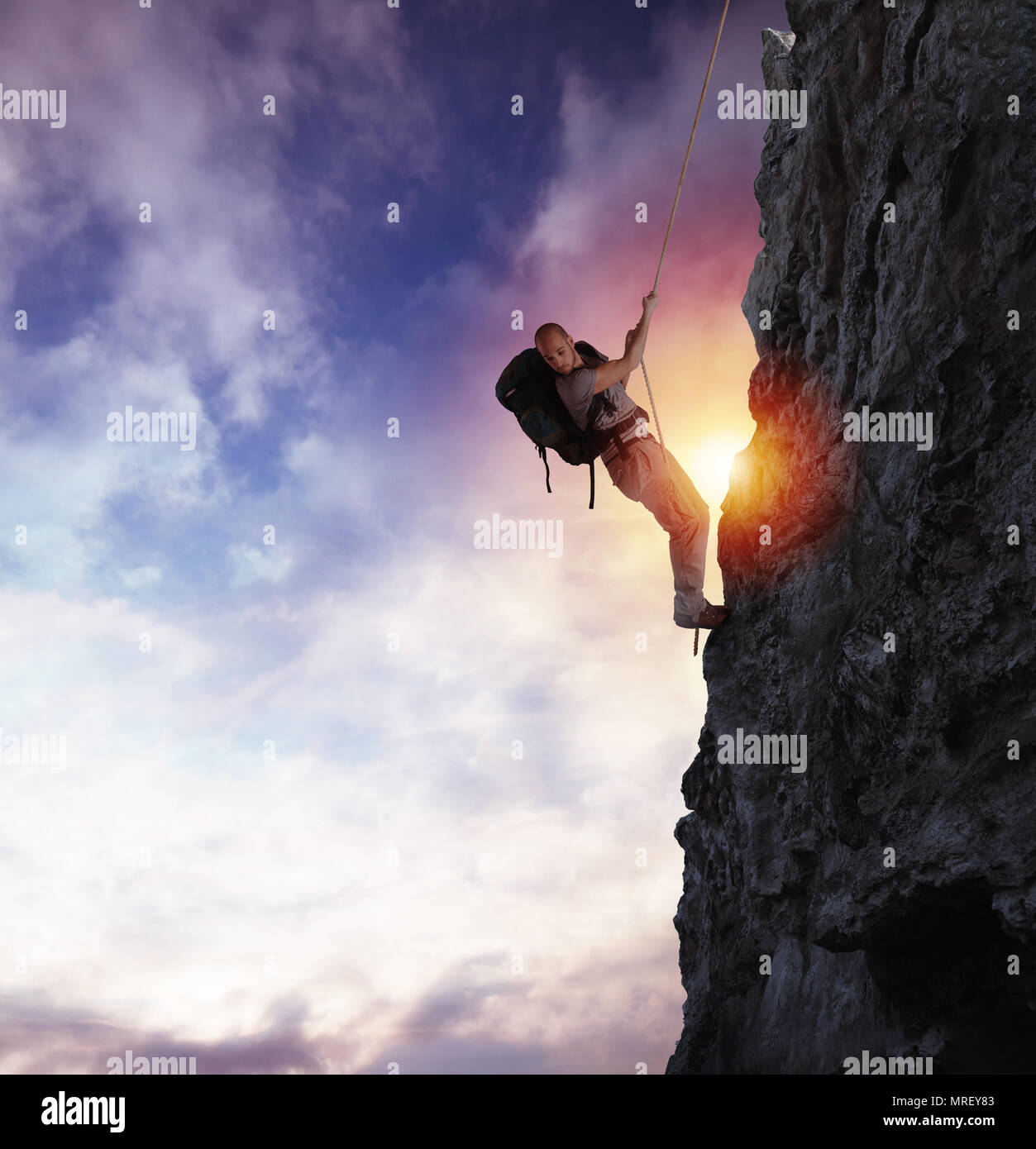 Man climbs a high danger mountain with a rope during sunset - Stock Image