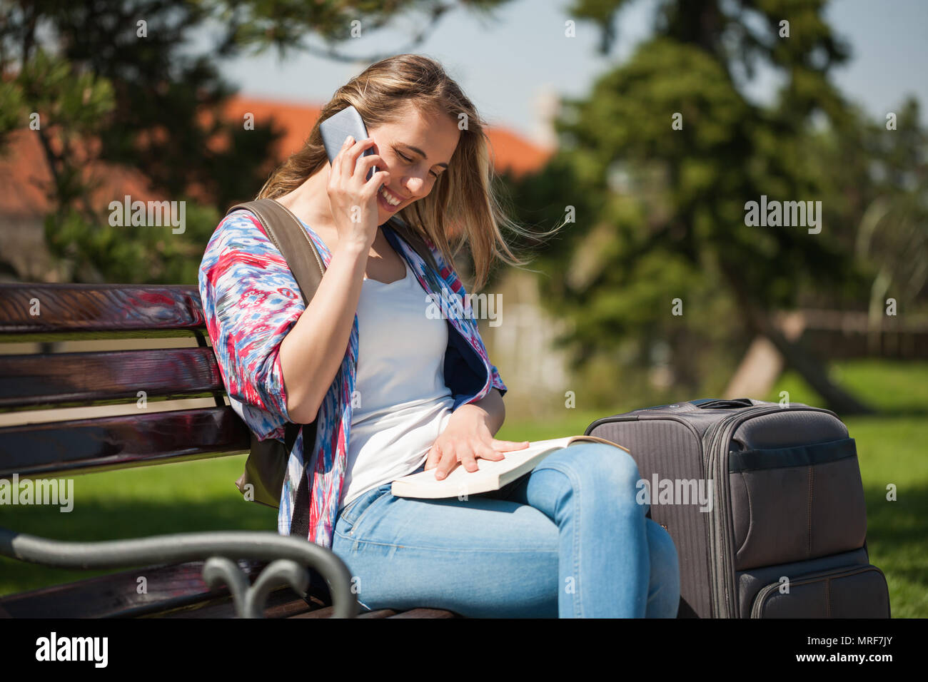 Young woman is going on city tour. She is looking city guide and talking on phone. - Stock Image