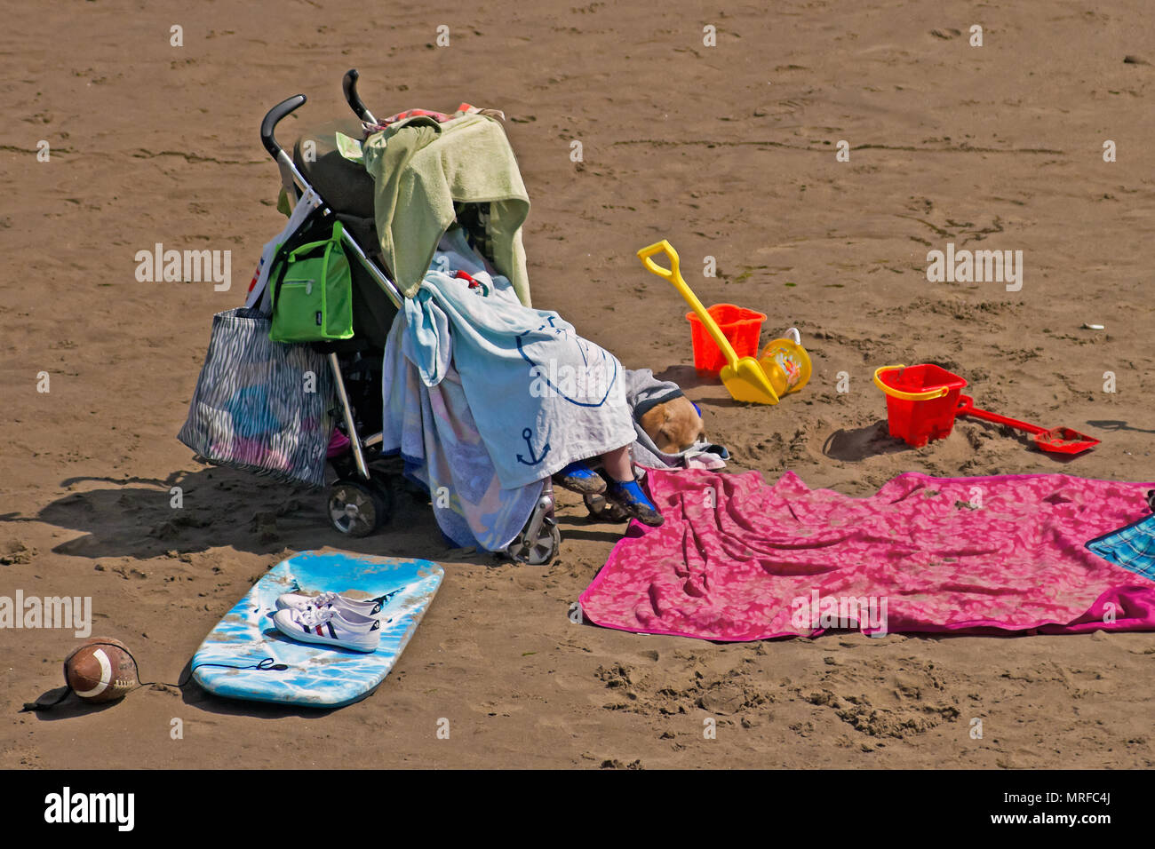 Sun-screened to the Max! Two sunbathers enjoy the summer sun on Scarborough's North Bay beach - Stock Image