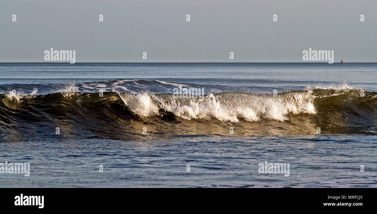 A breaking wave gently unrolls into the shallow waters of Scarborough's South Bay. - Stock Image