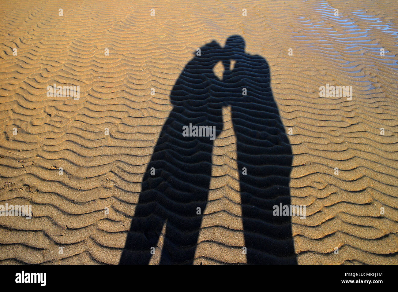 Shadow of two people kissing each other on beach. - Stock Image