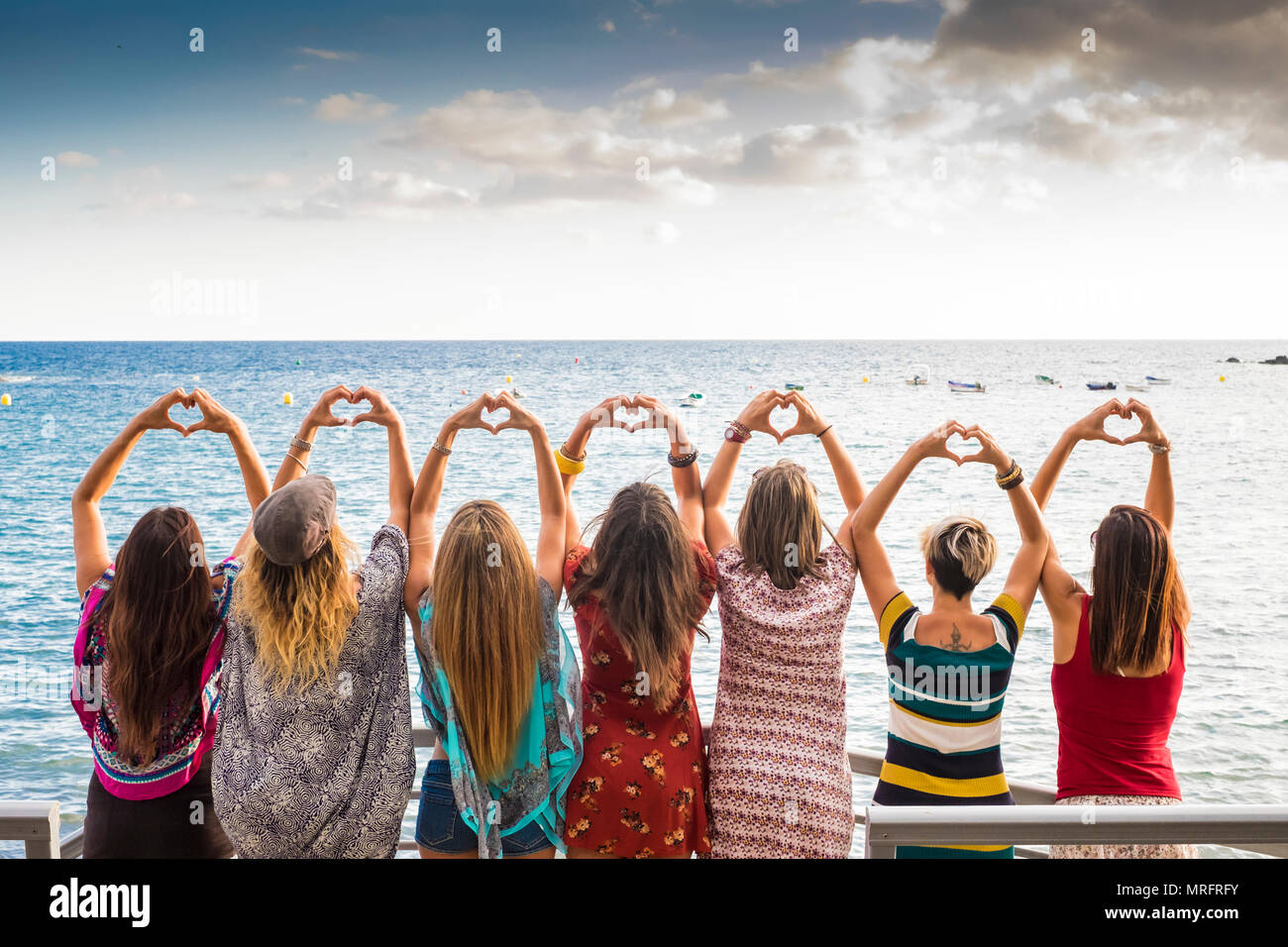 beautiful seven girls from the backside doing a heart with the hands looking at the ocean waiting the sunset in vacation leisure activity. friendshipt - Stock Image