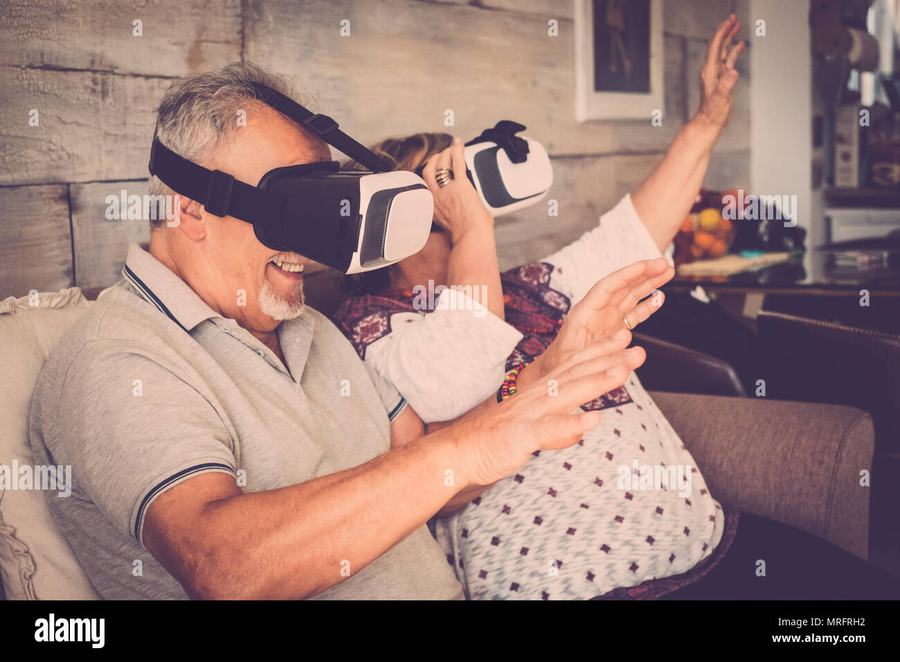 senior man and woman with goggles headset virtual reality eyeglasses playing and have fun sitting on the sofa at home. Warm filter and life together c - Stock Image