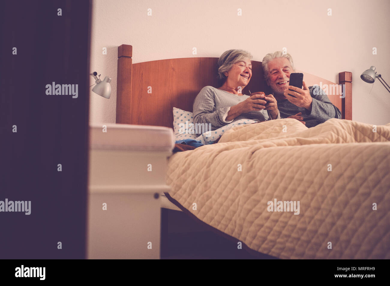 nice beautiful models couple of adult senior 70 years old having fun and enjoy in bed at home in bedroom. morning lazy wake up with no rush checking e - Stock Image
