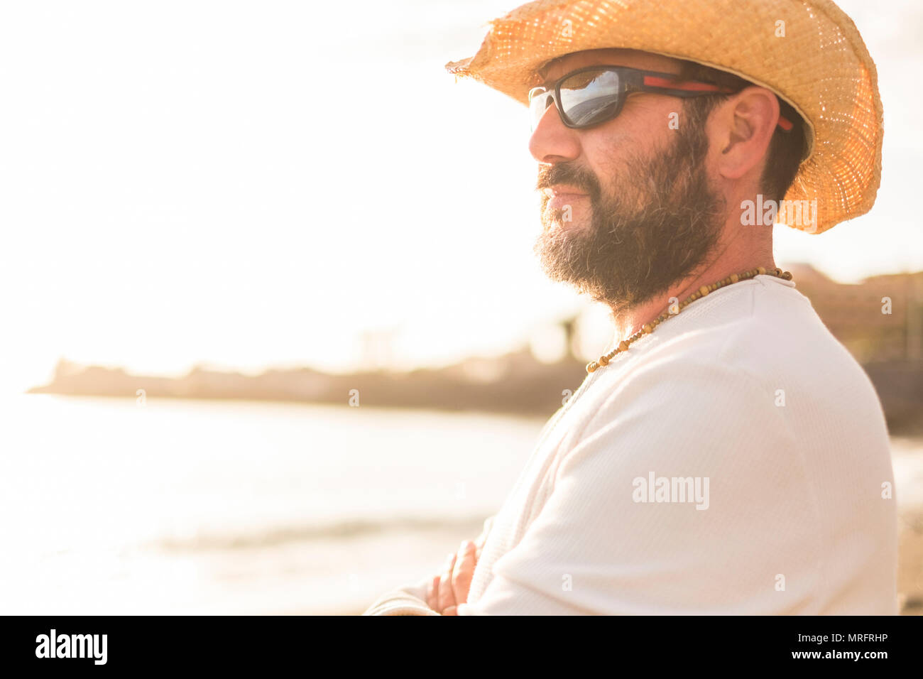 middle age 45 years old caucasian man in vacation look at the horizon with a golde sunset in the background. wearing sunglasses and summer clothes - Stock Image