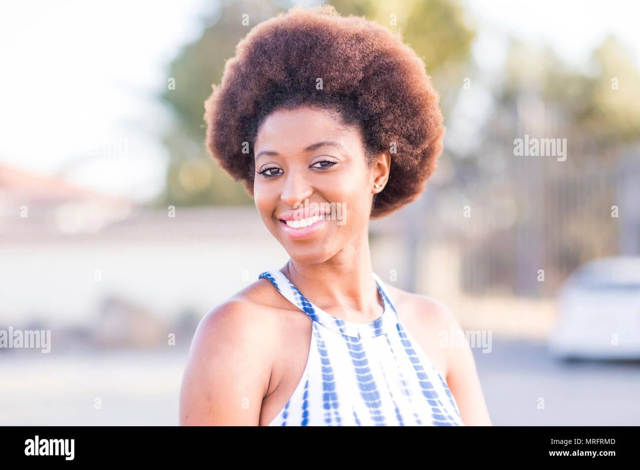 nice beautiful black race african model beautiful face and epression look at the camera. outdoor background portrait with natural light and joy - Stock Image