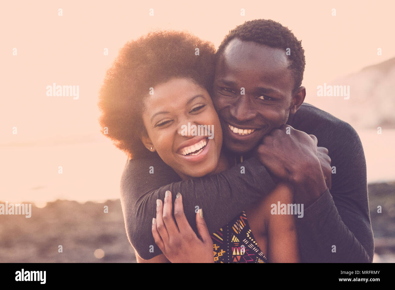 beautiful black race nice model couple man and woman young age hug and stay together with love and friendship. outdoor scenic place near the beach for - Stock Image