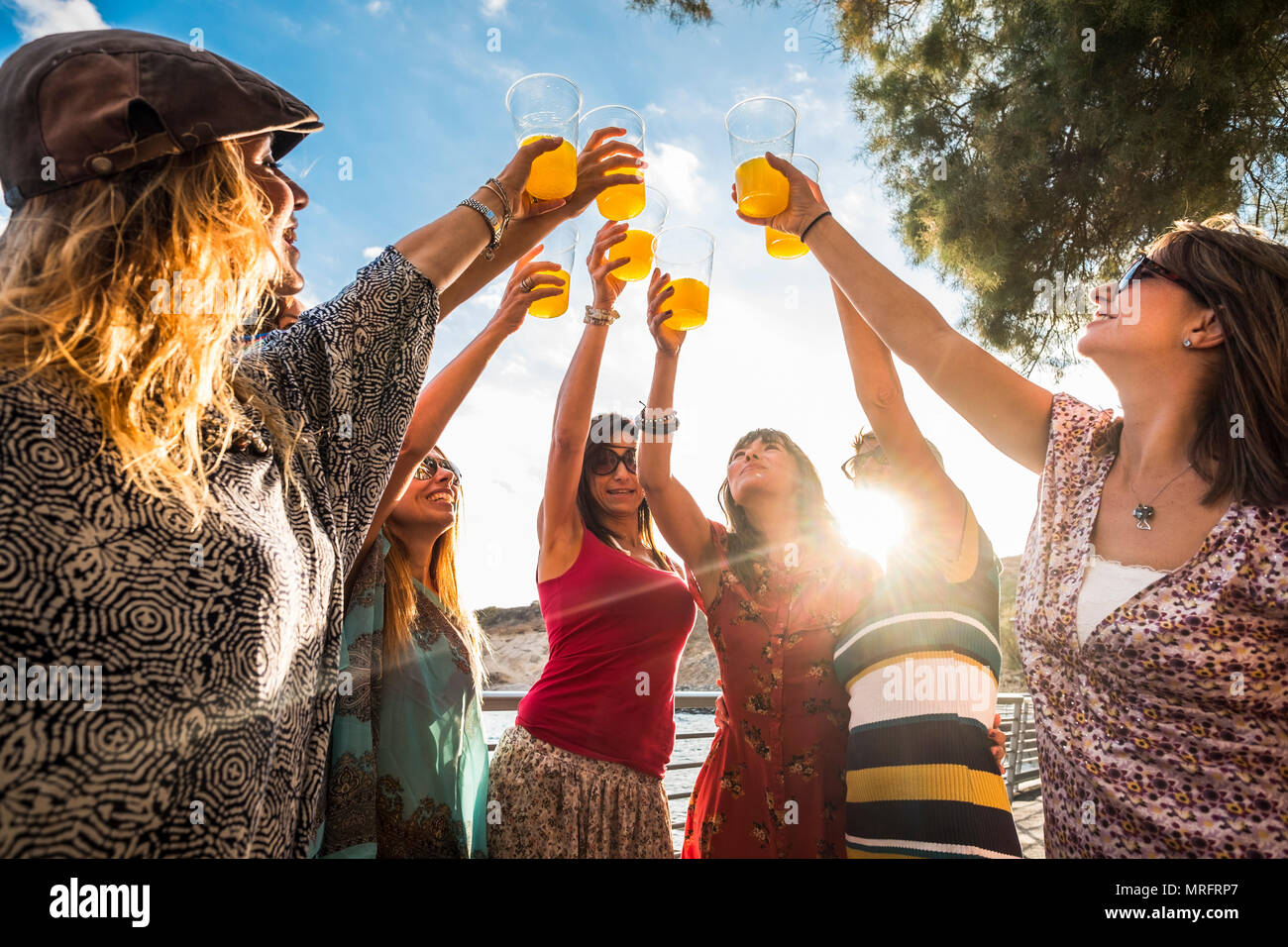 celebrating friendship or success team works outdoor with colored juice and 7 beautiful females friends all together with orange cocktail and the sunl - Stock Image