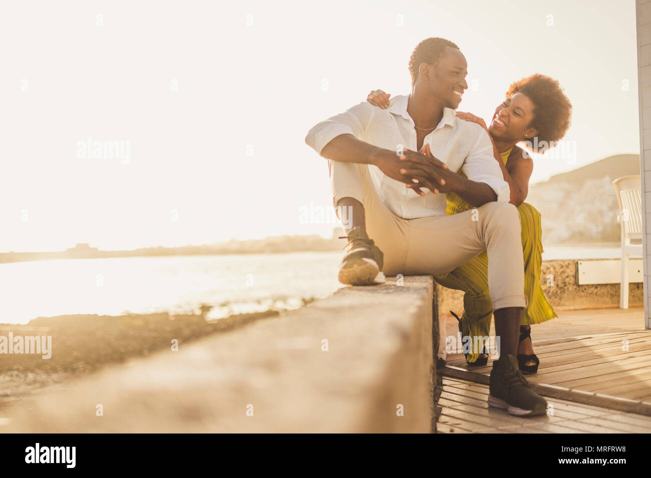 beautiful black race african couple in love and vacation sit down enjoying together with big smiles and laugh. casual clothes like fashion style with  - Stock Image