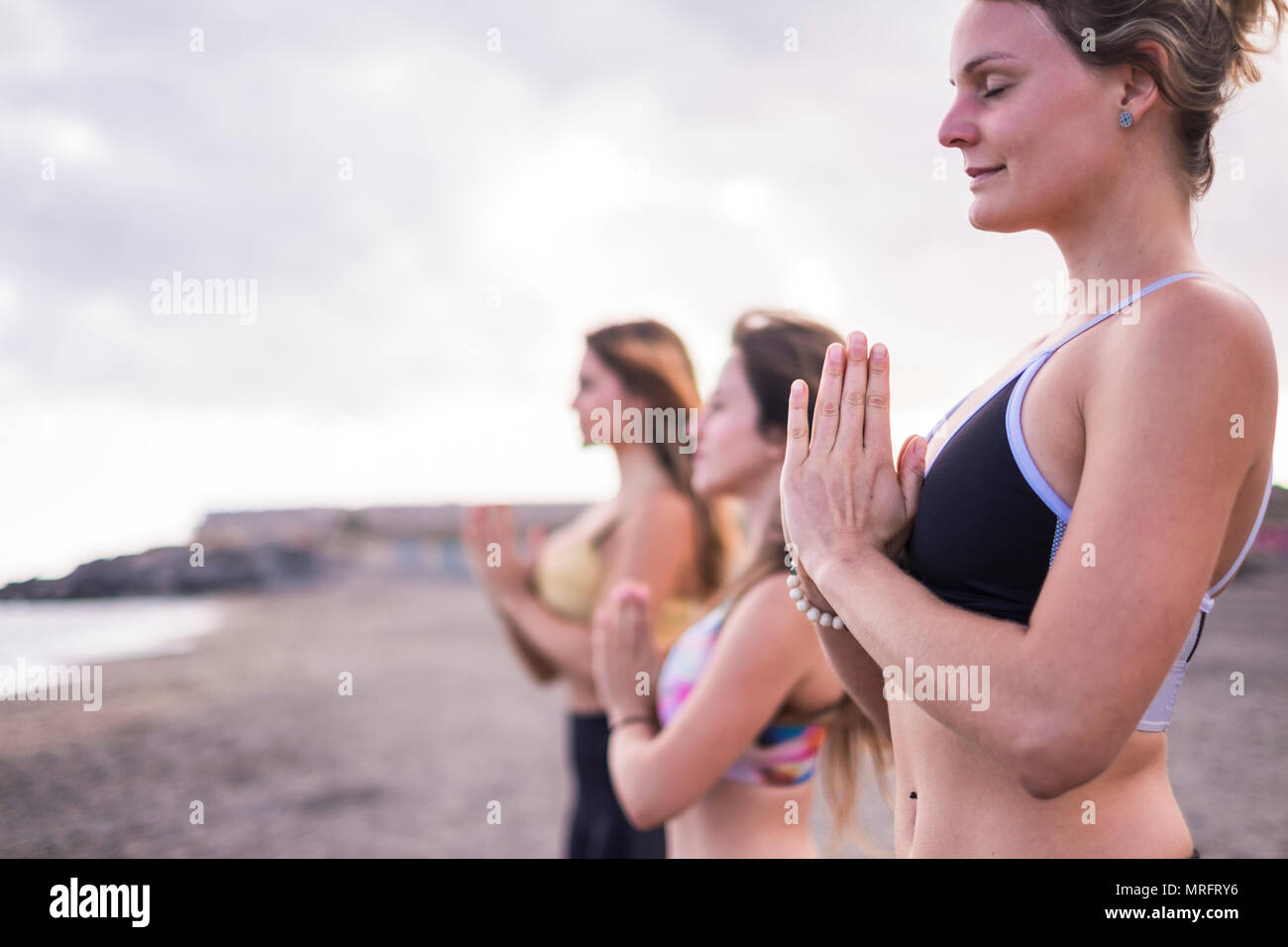 three caucasian beautiful young ladies doing yoga fitness pilates standing up balanced at the beach. outdoor leisure activity for friends having care  - Stock Image