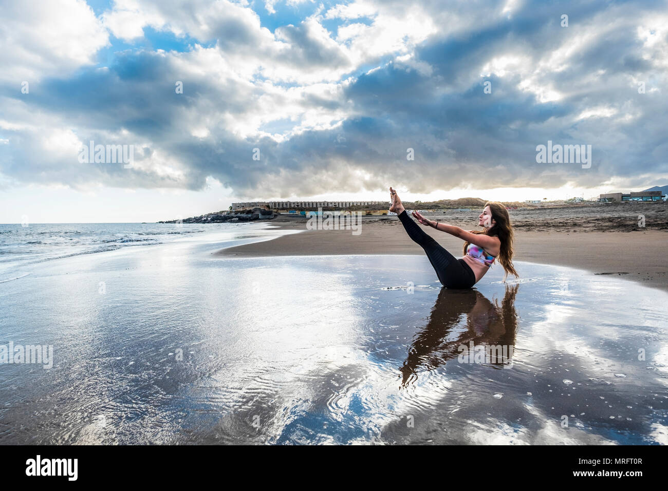 pilates fitness have care of body rest and stay position for young caucasian woman on the shore at the beach. scenic image for body health concept. yo - Stock Image