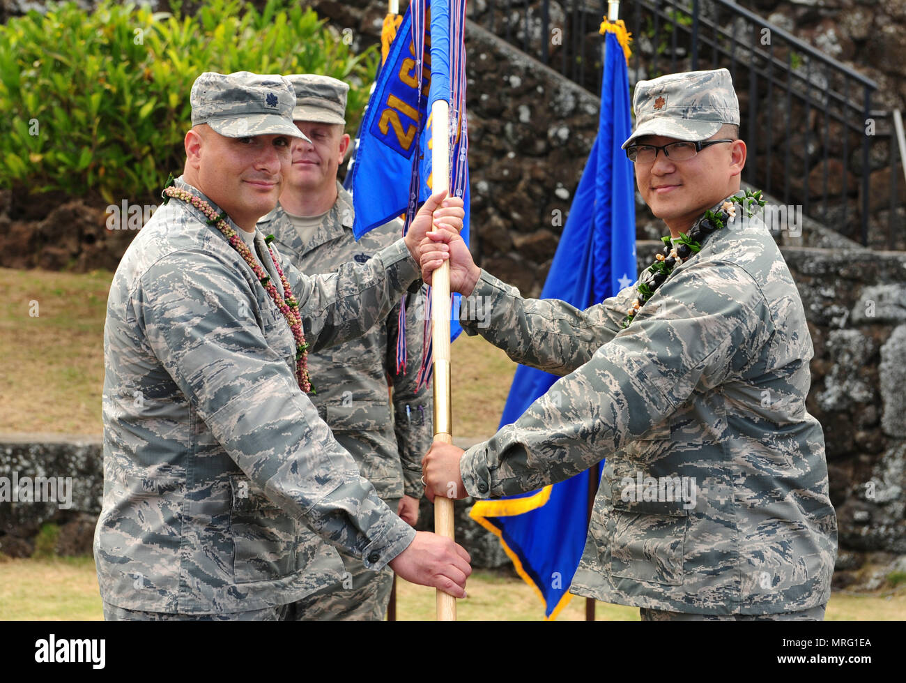Lt. Col. Phillip Verroco, 21st Space Operations Squadron commander, gives the detachment flag to Maj. Edmond Chan, Detachment 3 incoming commander, during the Detachment 3 Change of Command Ceremony, Kaena Point, Hawaii, June 9, 2017.  Detachment 3 is a component of the 21st Space Operations Squadron, 50th Network Operations Group, 50th Space Wing, and is located on the western tip of Oahu.  It is the oldest and one of seven worldwide remote tracking stations in the Air Force Satellite Control Network.  (U.S. Air Force photo by Tech. Sgt. Heather Redman) - Stock Image
