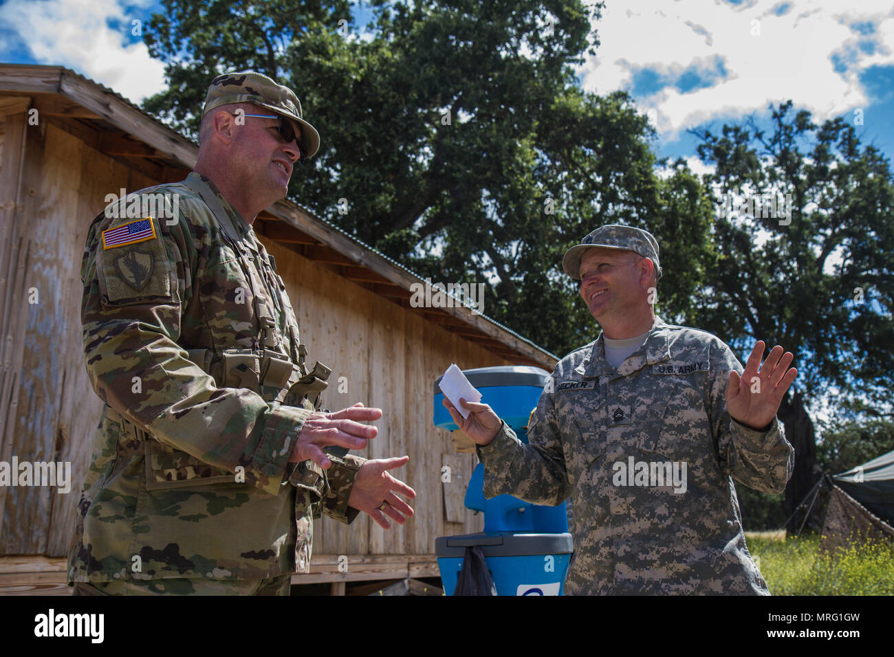 U.S. Army Master Sgt. Hugh Becker (right), 698th Quartermaster Co. from Nichols, New York, convenes with United States Army Reserve Command (USARC) Command Sgt. Maj. Ted Copeland on Tactical Assembly Area (TAA) Ward on Fort Hunter Liggett, Calif. on June 12, 2017. Becker is in charge of dining for TAA Ward and makes sure that all soldiers are fed while they are participating in the 91st Training Division's Warrior Exercise (WAREX) 91-17-03 at Fort Hunter Liggett, Calif. It is imperative that the soldiers engaging in the WAREX be kept well fed, so the exercise can produce combat ready forces. ( - Stock Image
