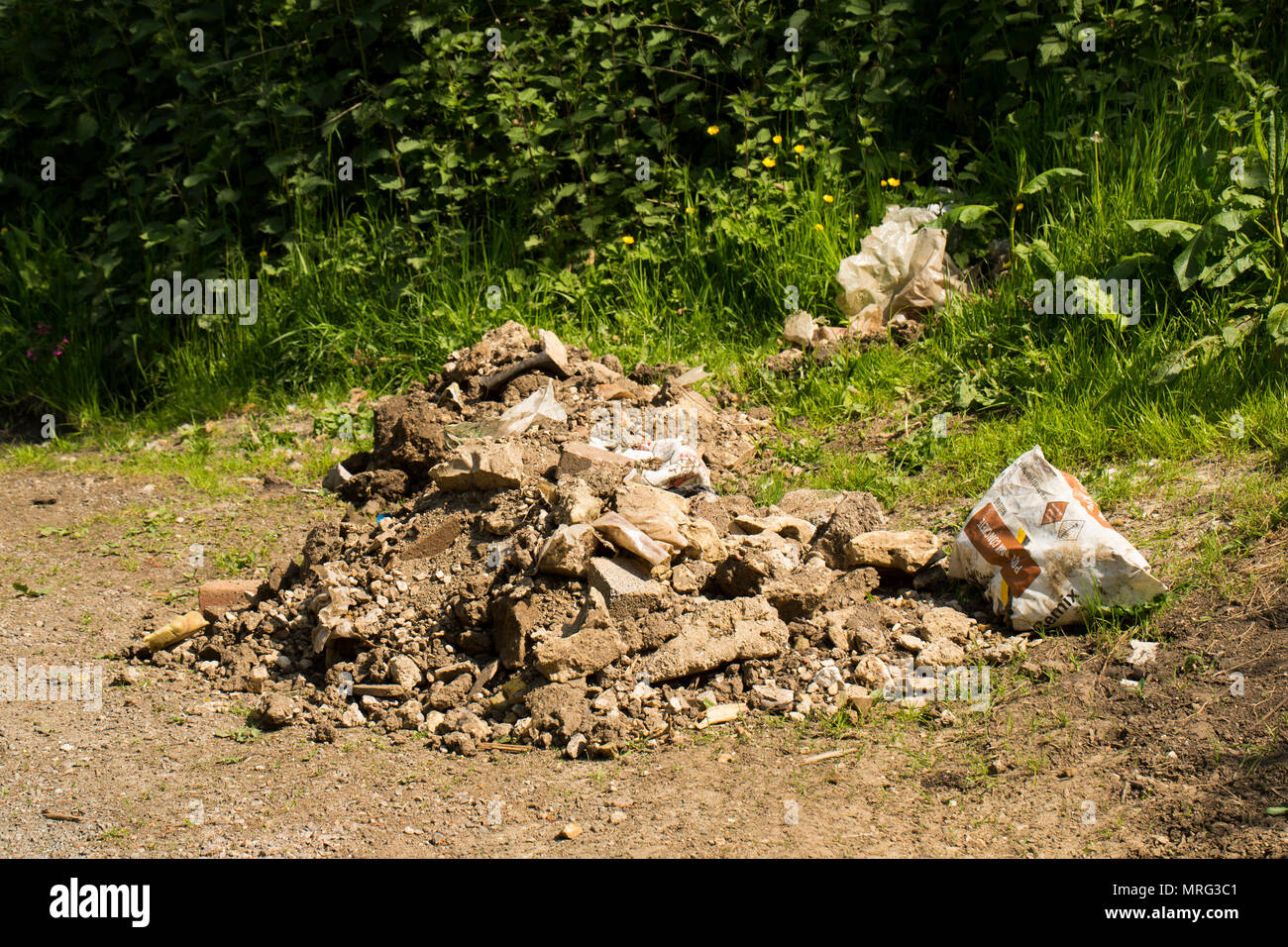 Rubble and bags dumped in a country lane in the entrance to a gate leading to a railway in North Dorset England UK GB - Stock Image