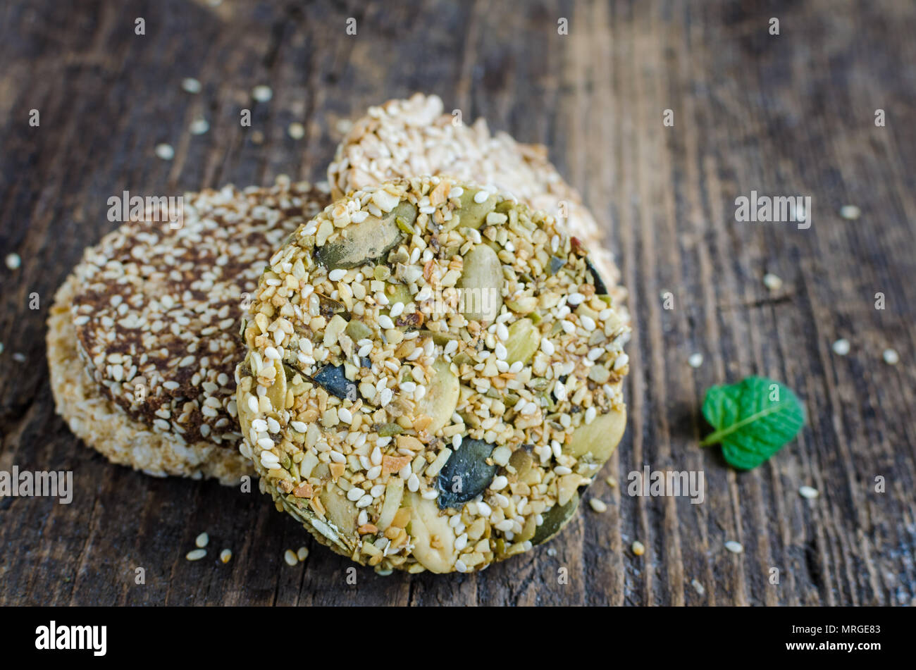 Dessert cereal snacks. Fitness dietary food. Kozinaki with sesame, peanuts, sunflower and pumpkin seeds and chocolate chip on old rustic wooden board, Stock Photo