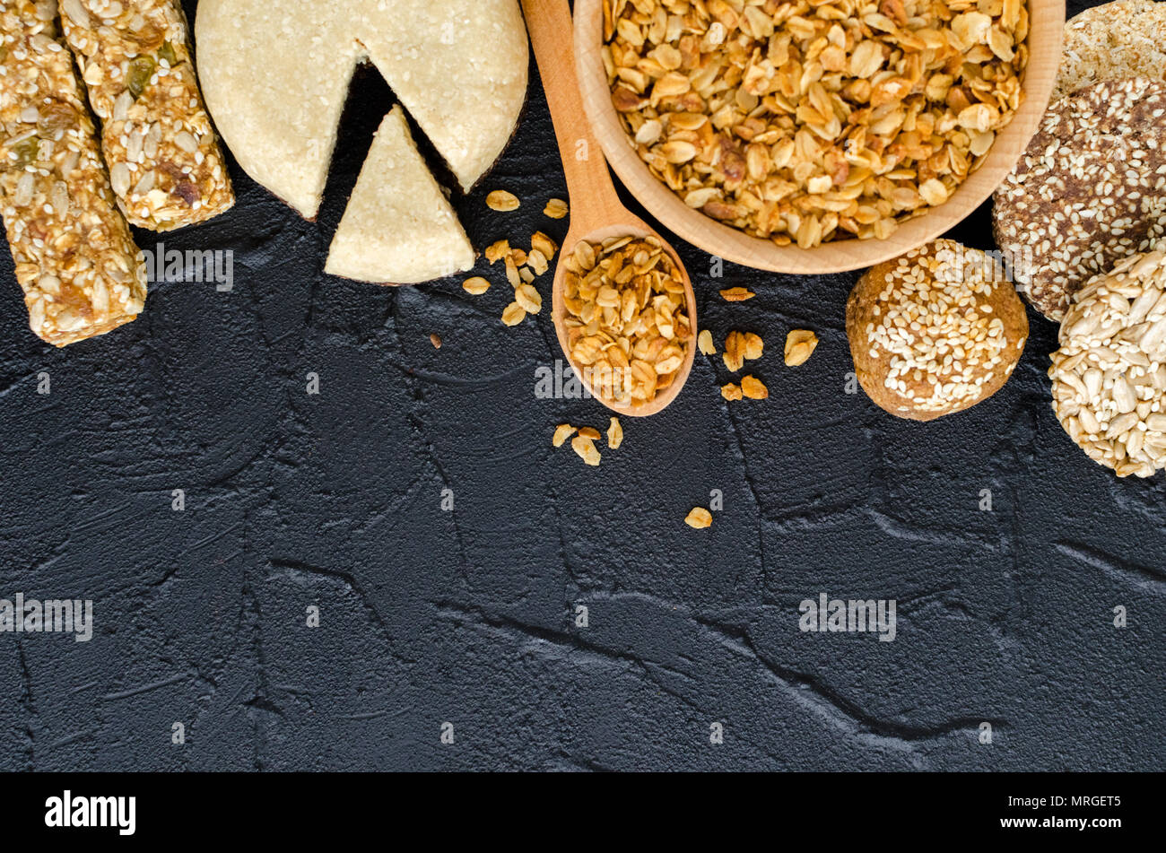 Healthy snacks. Fitness food. Sesame halva. Bowl and spoon with oat flakes, mint. Granola bars with flakes, sesame, sunflower and pumpkin seeds, raisi - Stock Image