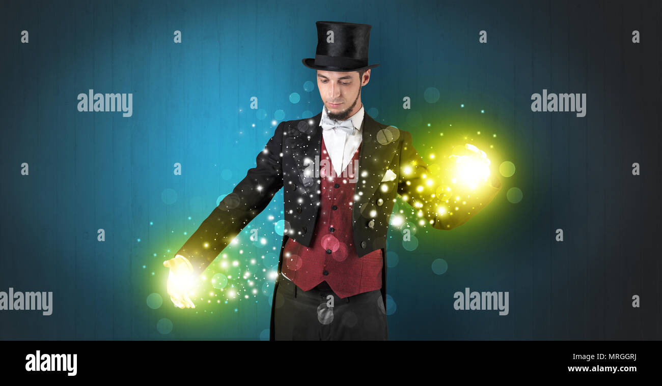 Handsome illusionist holding his superpower on his hands with gold wallpaper - Stock Image