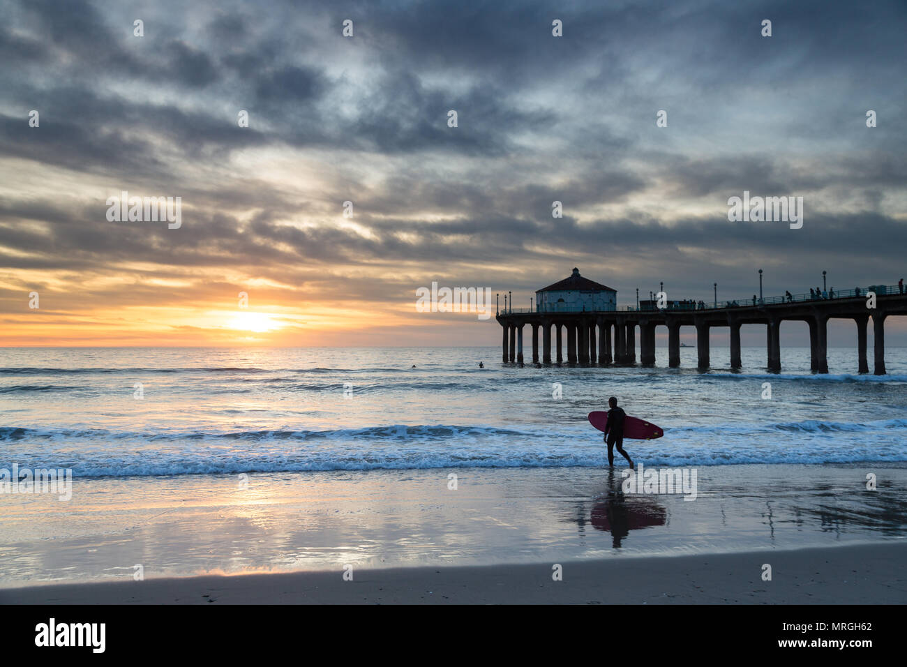 A longboard surfer walks into the ocean next to the Manhattan Beach Pier on a cloudy day, ready to get a few waves before dark. - Stock Image