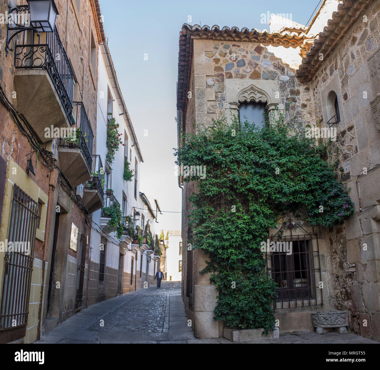 Caceres, Spain - 2017 october 17th: Visitor walking beside the Hospital of Pilgrim Knights, Caceres historic quarter, Spain - Stock Image