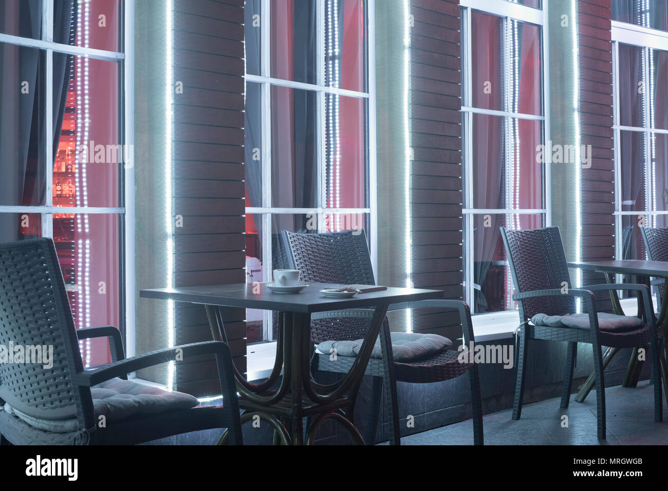 tables and chair in night cafe against the background of a window with a cup from under coffee - Stock Image