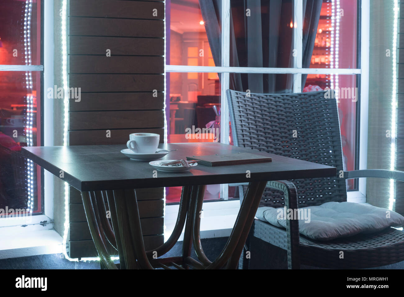 table and chair in night cafe with a mug from under coffee and the account against the background of a window - Stock Image