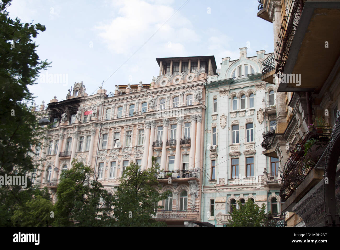 Old architecture buildings facades with stucco, sculptures and balconies - Stock Image