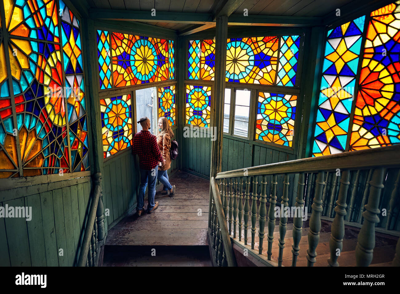 Romantic couple of tourist at balcony with stairs and colorful mosaic glasses in old Tbilisi, Georgia. - Stock Image