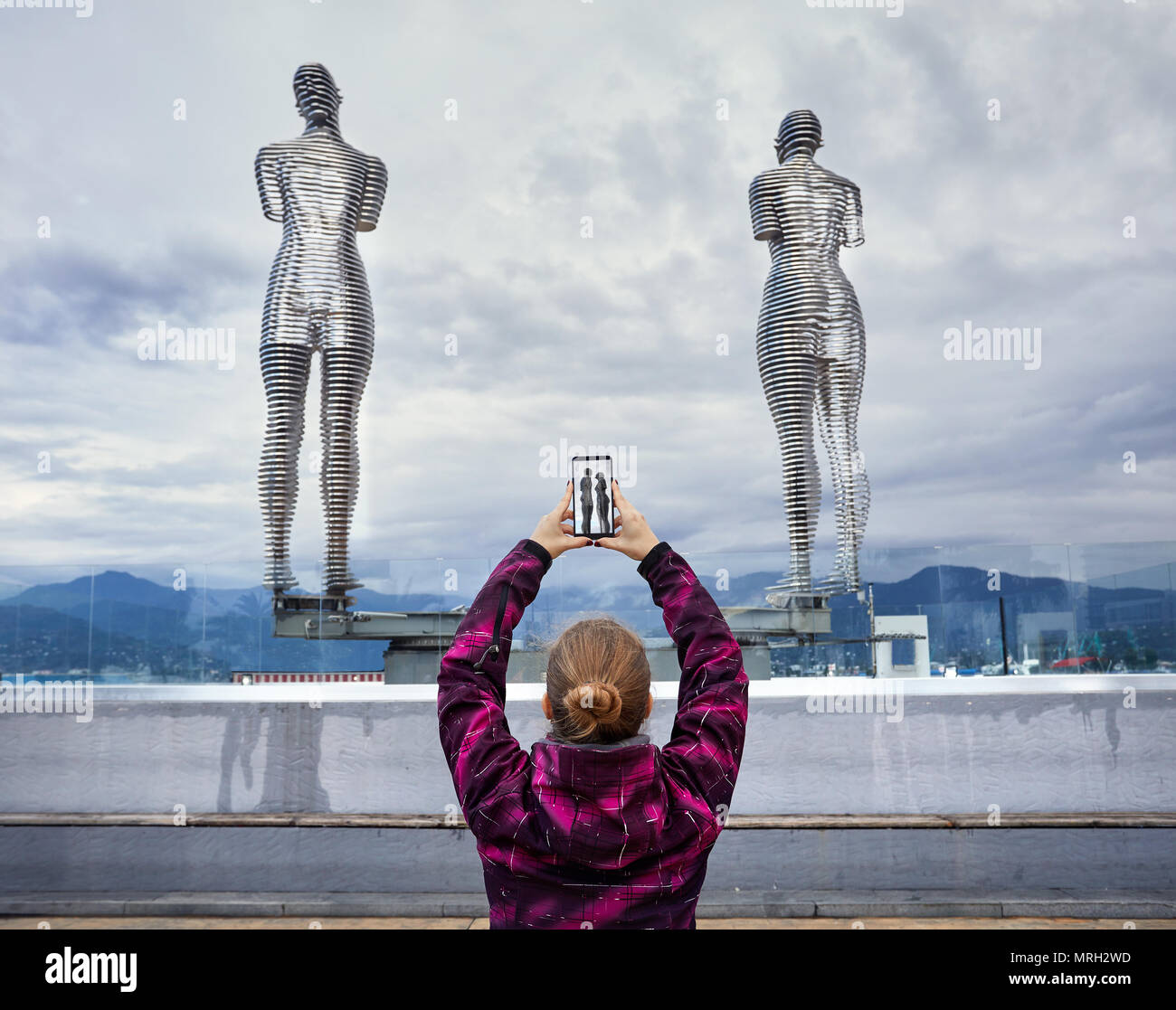 Tourist Woman tacking picture of statues Ali and Nino with smartphone in Batumi, Georgia - Stock Image