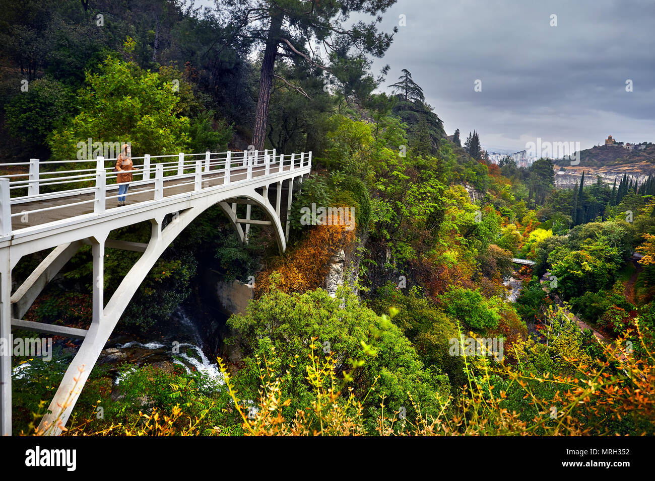 Tourist Woman in Hat at white bridge in Botanical Garden with autumn trees at overcast cloudy sky in Tbilisi, Georgia - Stock Image