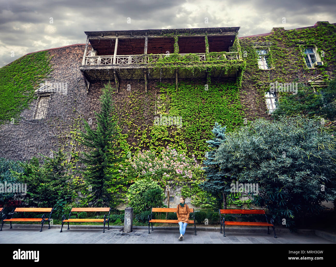Tourist woman on the branch near old building in central Tbilisi, Georgia - Stock Image