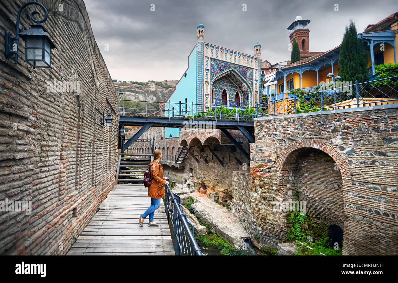 Tourist woman in brown jacket walking down the Old streets of Public Sulfuric bath district in central Tbilisi, Georgia - Stock Image