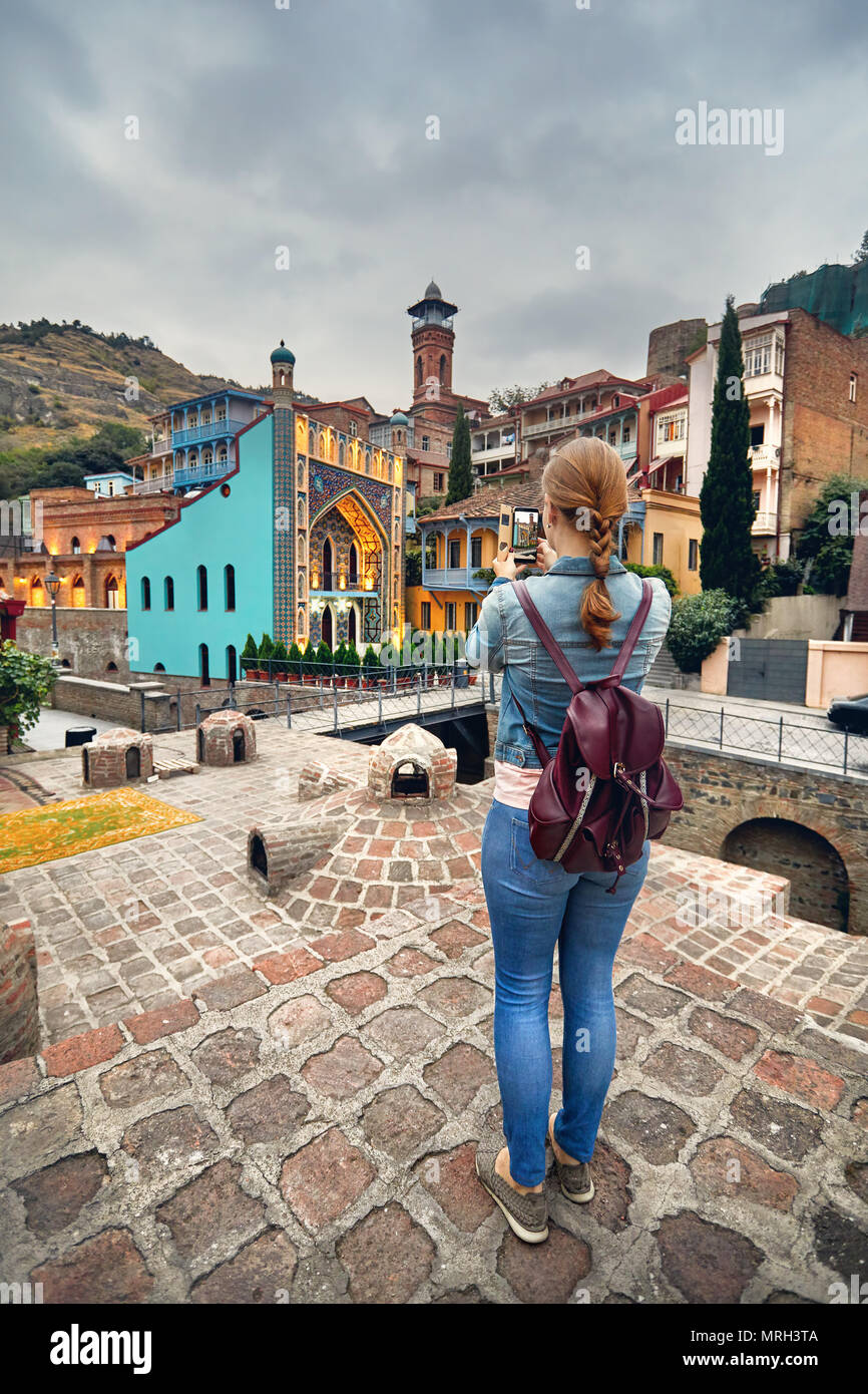 Tourist woman in brown jacket Taking picture of Public Sulfuric bath by her smartphone in Tbilisi, Georgia Stock Photo
