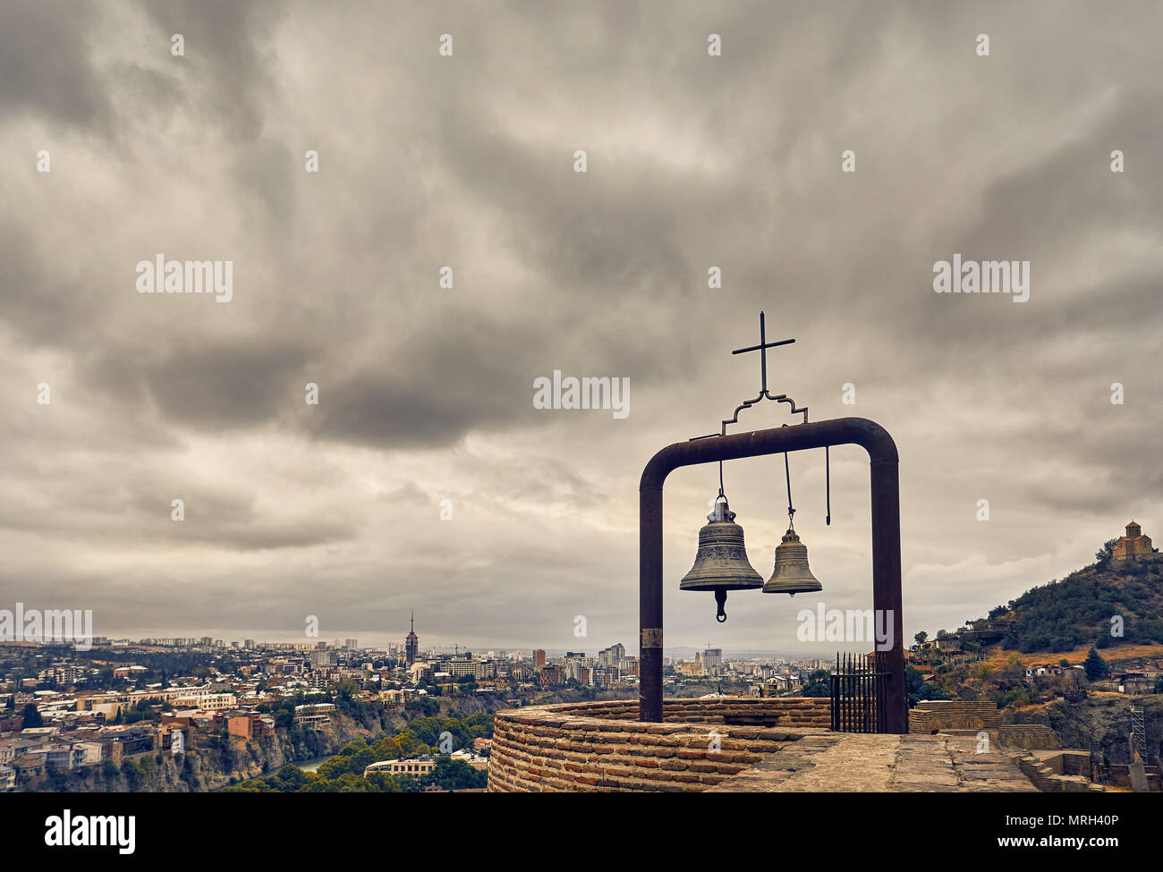 Old medieval castle Narikala with big bells on the wall at overcast cloudy sky in Tbilisi, Georgia - Stock Image
