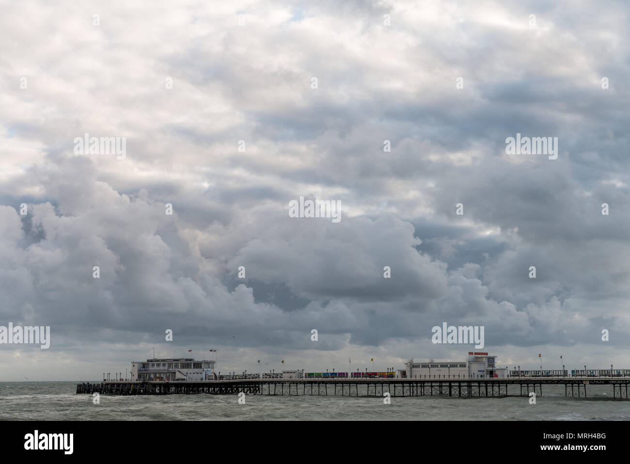 Large dark clouds in the sky above Worthing Pier in Worthing, West Sussex, England, UK. - Stock Image