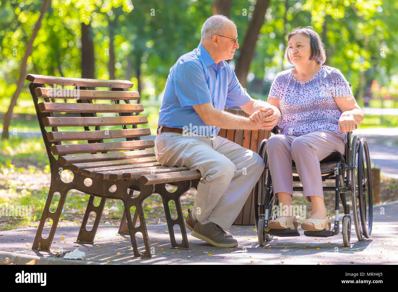 Elderly man strengthens his wife in the wheelchair outside the summer park. - Stock Image