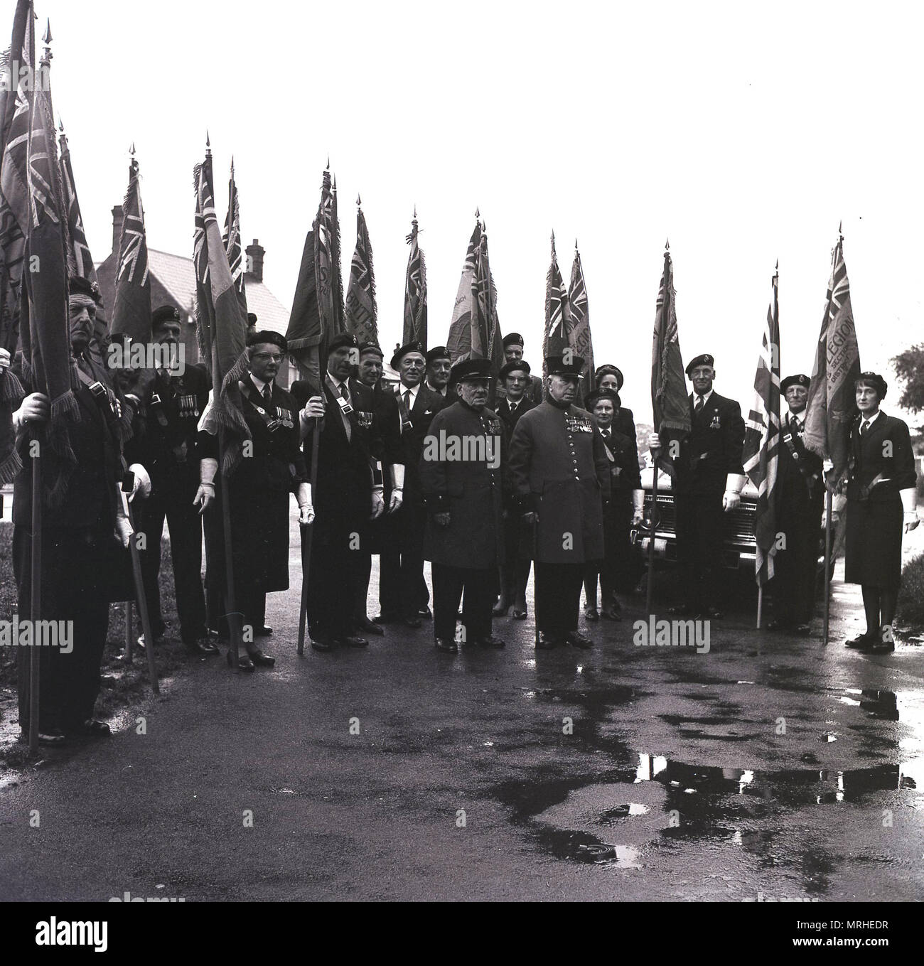 1964, historical, veteran soldiers of the British Armed Forces with regimental flags line-up gather outside on a wet road before a remembrance sunday march for the armed services charity, the Royal British Legion, Bucks, England, UK. - Stock Image