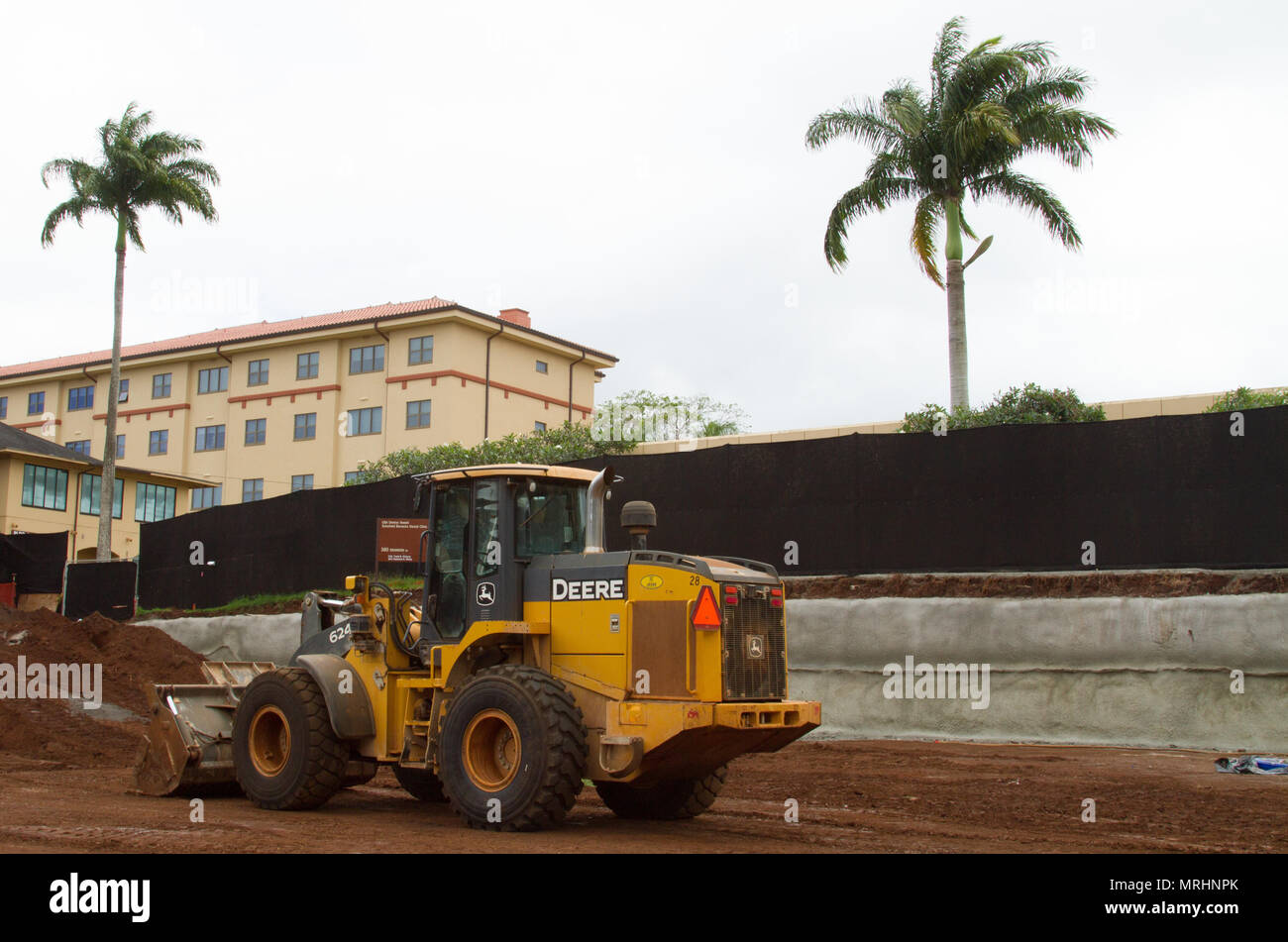 SCHOFIELD BARRACKS, Hawaii — A construction tractor rests in the dirt between its barrier and the clinic buildings that stand tall behind it. Swinerton Builders have been excavating and constructing within an area neighboring McCornack Road and the U.S. Army Health Clinic, here, before and after May 24. Employees of the company are manufacturing the new building that will provide a wider range of parking options for soldiers and civilians alike to use while under care at the clinic. Stock Photo
