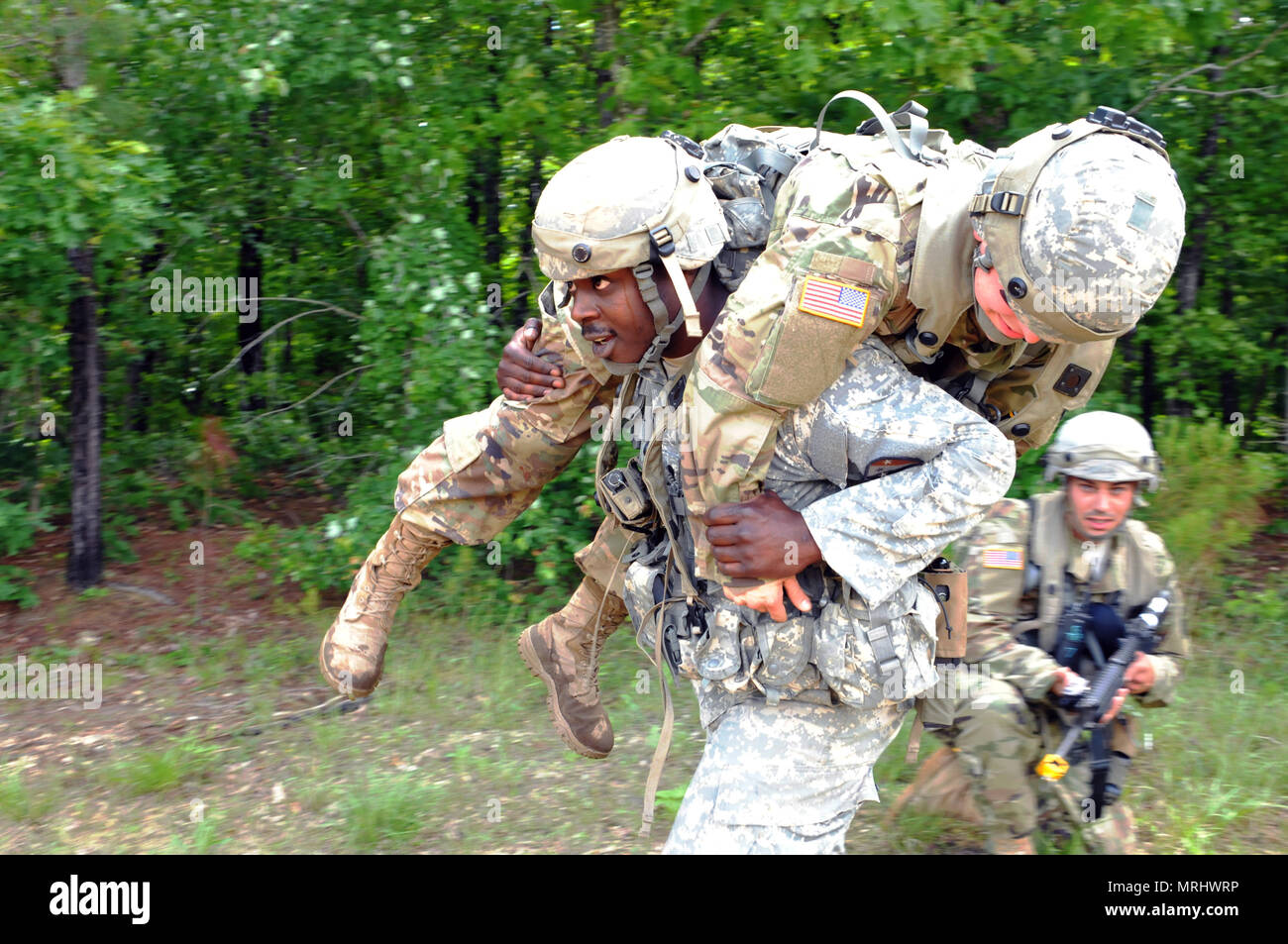 On 25 May 2017, during annual training at Fort Pickett Va., New Jersey Army National Guard Spc. Paul Daniels of the 250th Brigade Support Battalion fireman carries a fellow Soldier during a casualty evacuation exercise while Spc. Edgar Sepulveda provides overwatch. More than 3,000 New Jersey Army National Guard Soldiers - more than half of the combat strength of the force - is participating in the eXportable Combat Training Capability (XCTC) rotation from May 20 through June 9. (New Jersey Army National Guard photo by Sgt. 1st Class Joe Donnelly/RELEASED) - Stock Image