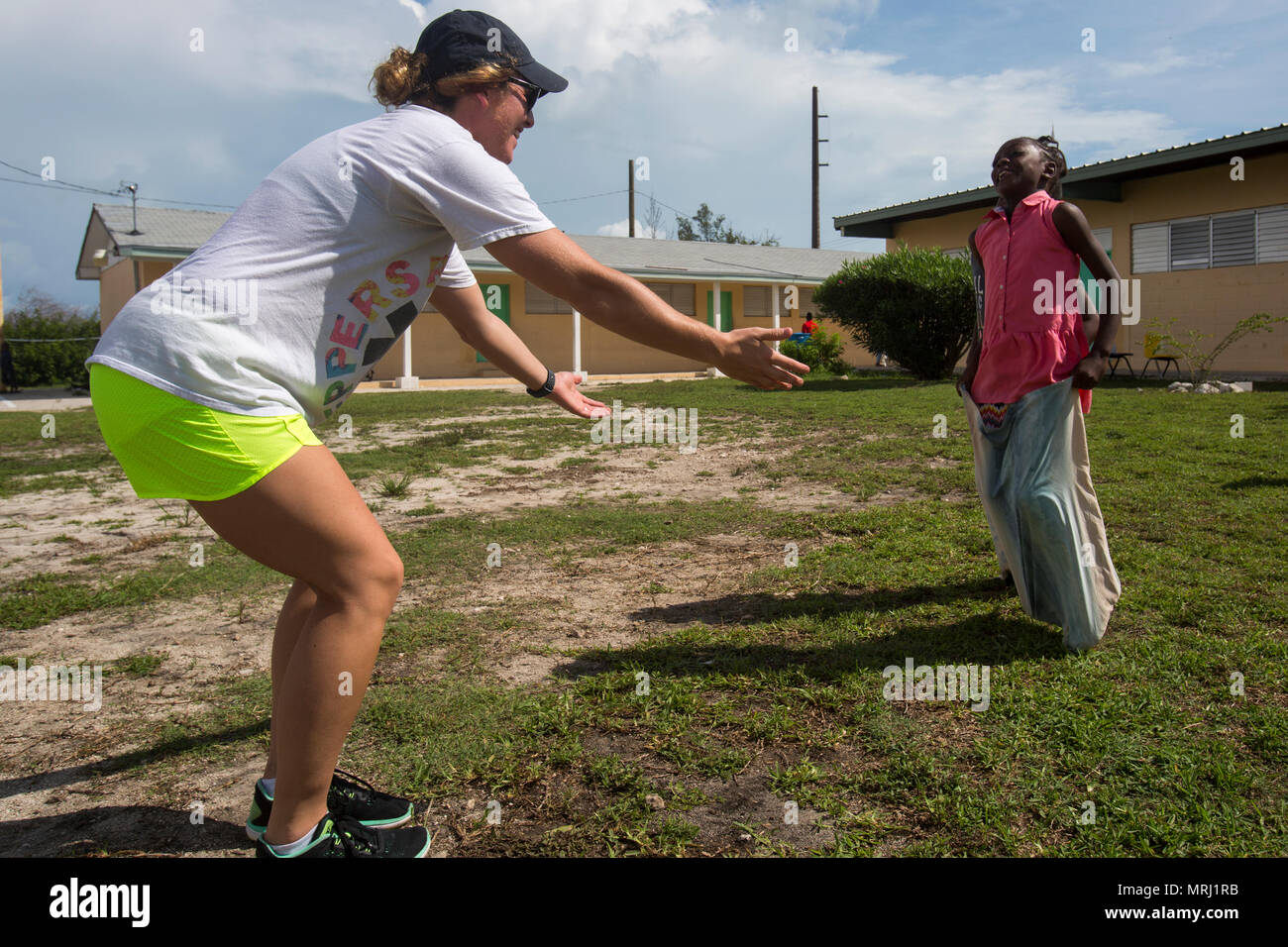Cpl. Haeli Graham, a wireman with 8th Communications Battalion, judges a sack race at the West End Primary School near Freeport, Bahamas, June 16, 2017. U.S. Marines representing the Marine Headquarters Group and Navy sailors aboard the USS Iwo Jima volunteered their time to restoring the life and color into the school after the community was devastated by the recent Hurricane Matthew. (U.S. Marine Corps photo by Sgt. Michelle Reif.) - Stock Image