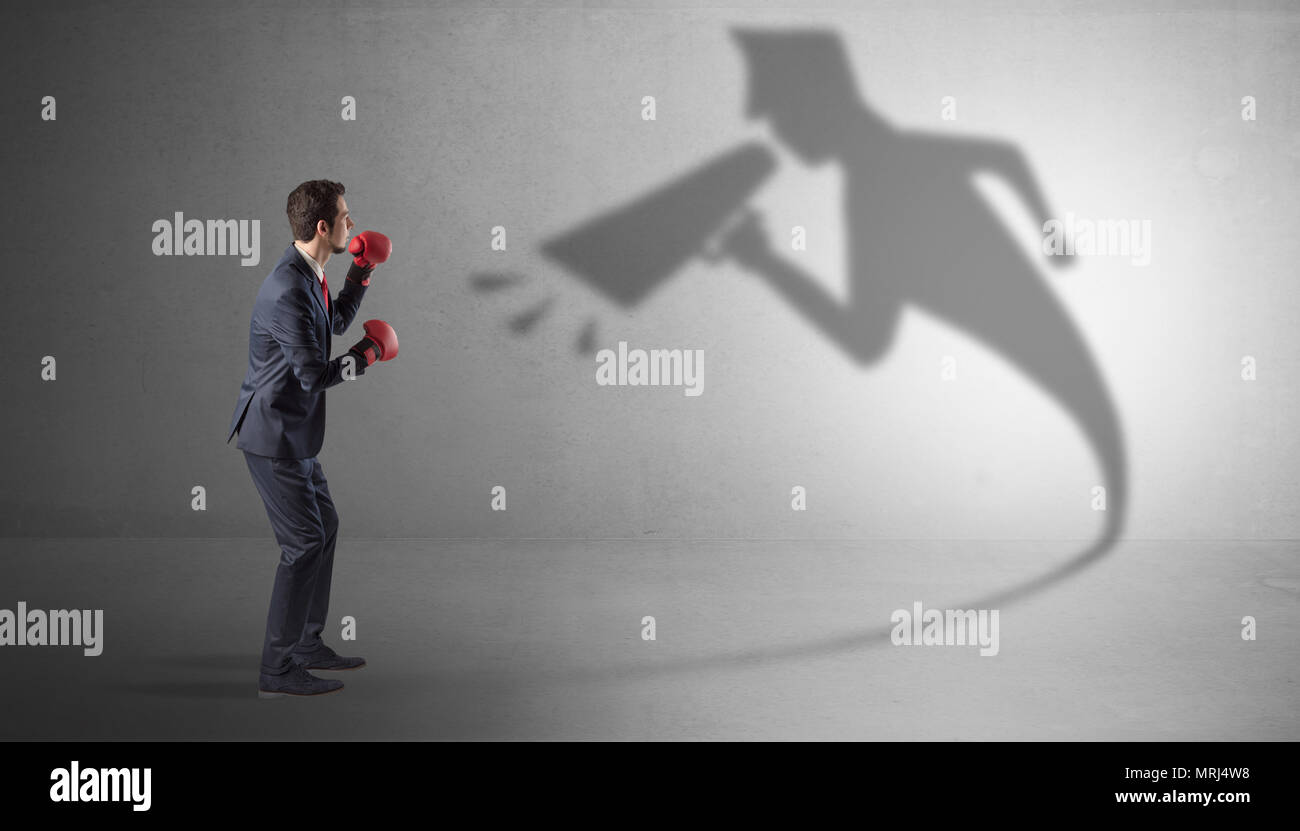 Businessman fighting with his bossy yelling shadow  - Stock Image