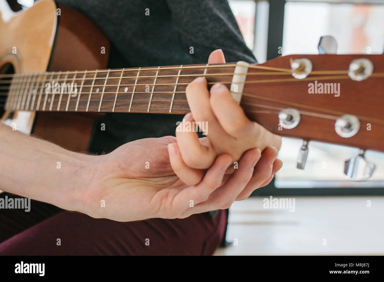 Learning to play the guitar. Music education and extracurricular lessons - Stock Image