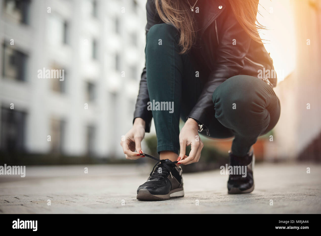 Young attractive girl ties shoelaces. next to skyscraper - Stock Image