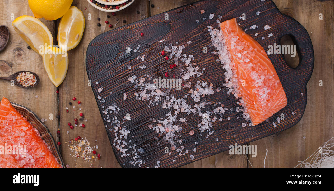 Raw salmon fillet with pepper sweetbread and salt on baking paper rustic theme with copy-space. Flat lay - Stock Image