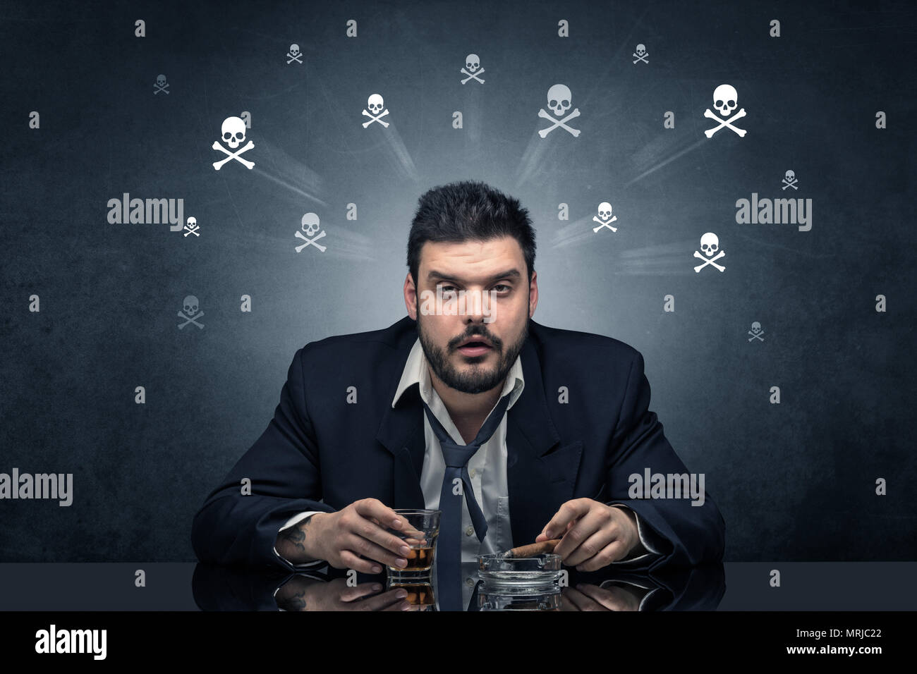 Loser drunk man sitting at table with skulls concept around  - Stock Image