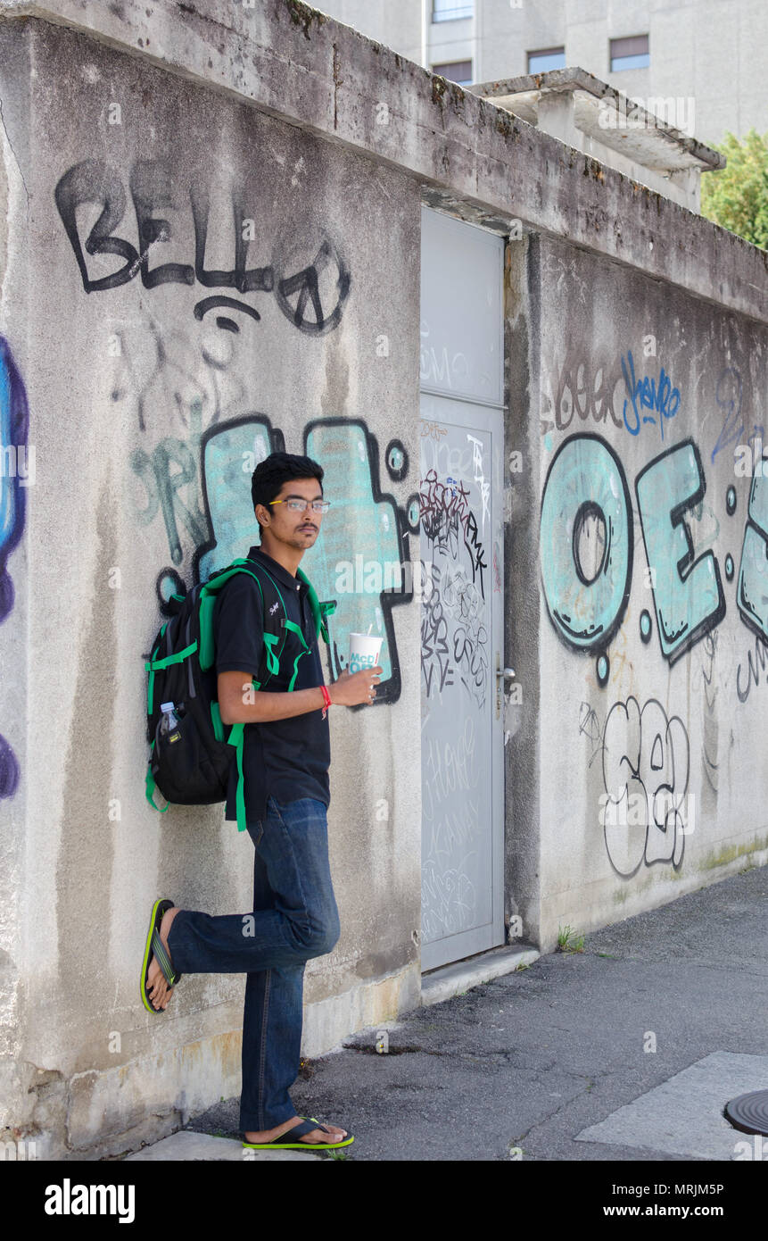Full Length Portrait Of Young Adult Indian Boy Posing Against Graffiti Wall With Backpack Looking
