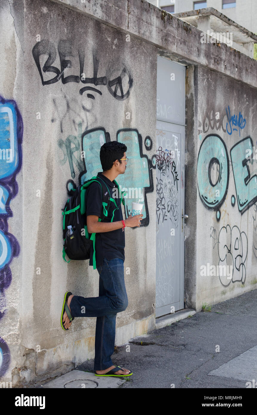 Full length portrait of young adult Indian boy posing against graffiti wall with backpack, looking away from camera. - Stock Image