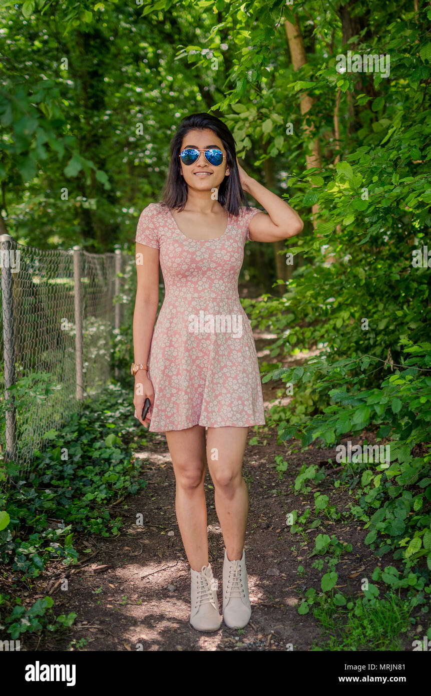 Full length portrait of a cute smiling girl in pink one piece dress, wearing blue aviator sunglasses, posing on a forest path / nature background. - Stock Image