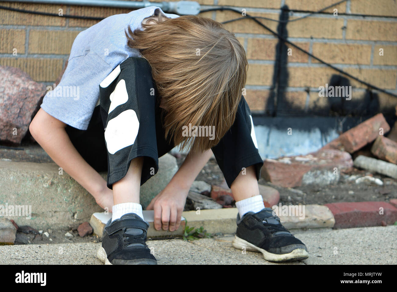 young boy defeated, down and out - Stock Image