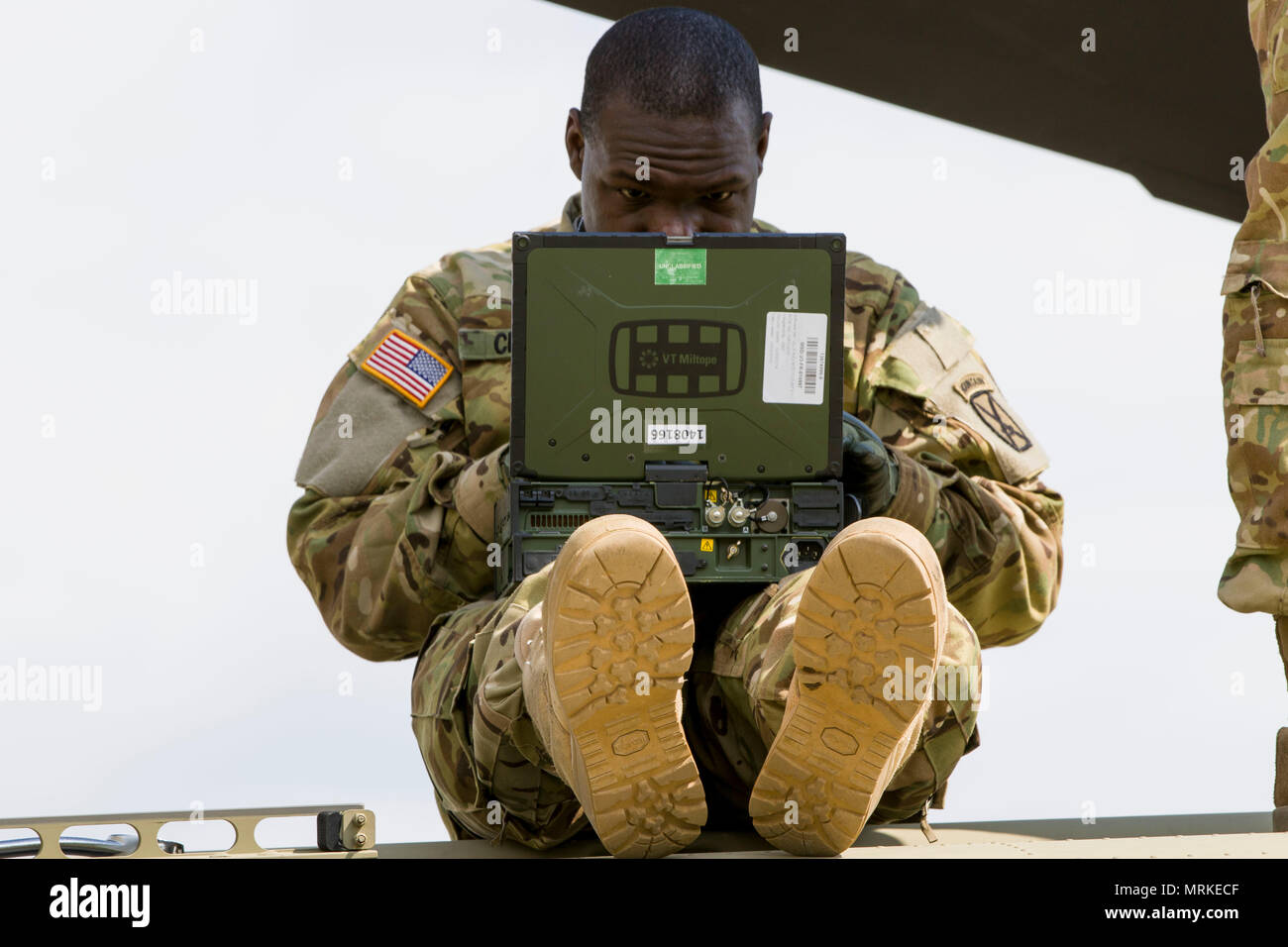 A Soldier from D Company, 3-10 General Support Aviation Battalion, refers to repair procedures during the replacement of the aft yoke in a CH-47 Chinook helicopter at Lielvarde, Latvia, on May 19. The highest ranking member of the team was a specialist; empowering junior leaders is imperative to be successful in the spread-out environment of U.S. Army Europe's Atlantic Resolve mission. (U.S. Army photo by Spc. Thomas Scaggs) 170519-A-TZ475-037 - Stock Image