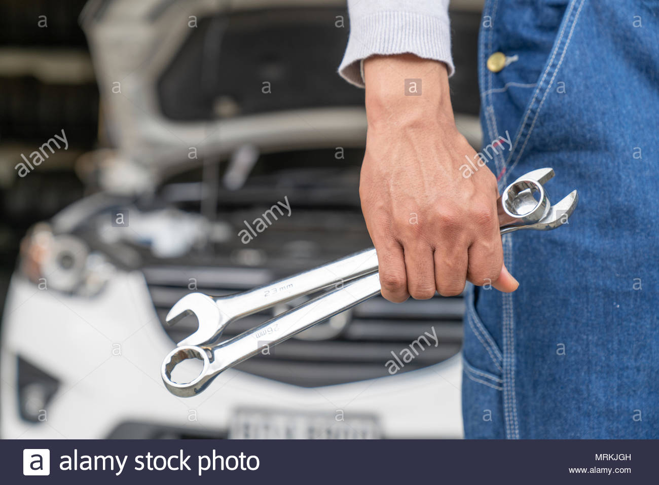 Car repairing,Hand of car technician auto mechanic with a wrench working in garage. Repair service ,car repair station.vintage tone Stock Photo